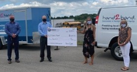 Image Description.  Union Bank employees present donation check to Hand2Hand representatives.
