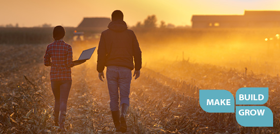 Image Description.  Two farmers walking through harvested field at sunset.